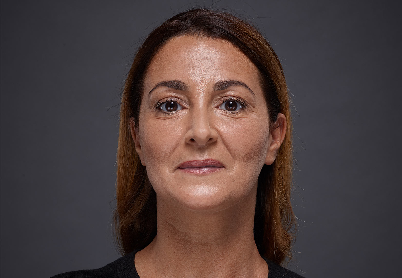 Woman face with brown eyes and brown hairs on grey background | Fillmed